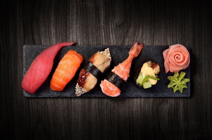 Sushi on black stone slate plate, black wooden background.